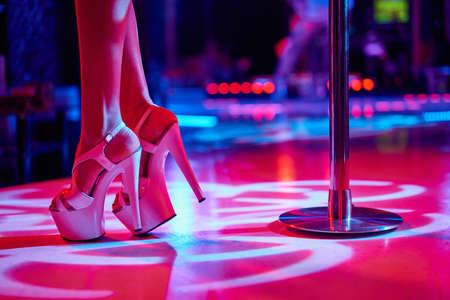 Jeune femme pole dancing strip-tease avec pylône en boîte de nuit. Belle fille sur scène. Belles jambes féminines en bandes de chaussures à talons hauts Banque d'images