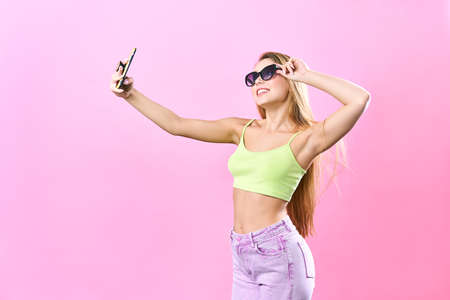 Close-up portrait of young cheerful readhead woman in summer wear makes selfie on smartphone, over pink background Banco de Imagens