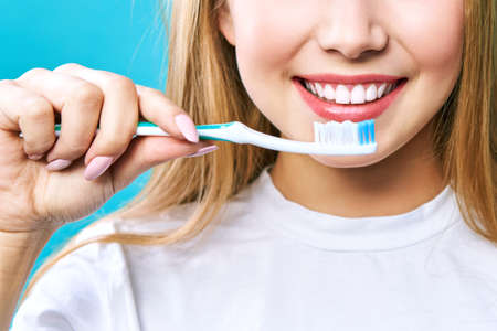 Young beautiful woman is engaged in cleaning teeth. Beautiful smile healthy white teeth. A girl holds a toothbrush. The concept of oral hygiene. Promotional image for a stomatology, dental clinic Imagens