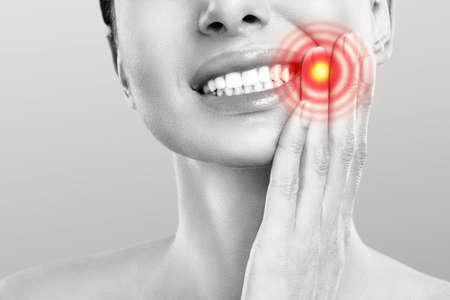 Dolore ai denti e odontoiatria. Giovane donna che soffre di forte dolore ai denti, toccando la guancia con la mano. Mal di denti doloroso di sensibilità femminile. Concetto di cura dell'odontoiatria Archivio Fotografico