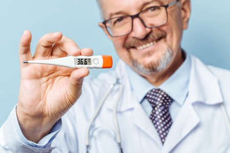 Portrait of a handsome senior doctor holding a thermometer in his hands, on a thermometer, the normal temperature of a healthy person is 36.6 degrees Celsius. Healthcare concept, flu prevention.