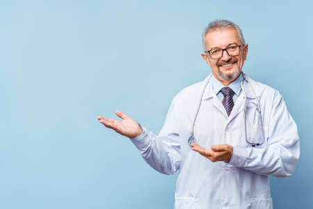 Cheerful mature doctor posing and smiling at camera, healthcare and medicine. Isolate on blue background.
