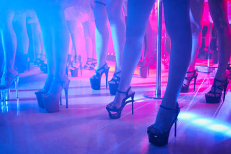 Young sexy woman pole dancing striptease with pylon in night club. Beautiful naked stripper girl on stage. Beautiful female legs in high-heeled shoes strips