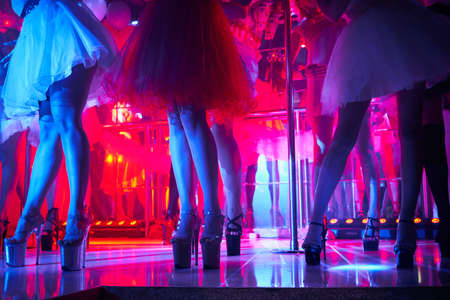 Young sexy womans pole dancing striptease in night club. Beautiful naked stripper girl on stage. Beautiful female legs in high-heeled shoes strips Stock Photo