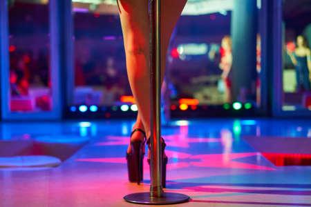 Absätze von Poledance oder Striptease der Frau. Pylon im Nachtclub. Stripperin Hintergrund