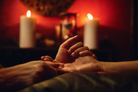 A woman does acupressure fingers for a man. hand massage with intimate lighting. Prelude before making love. Close. Complete relaxation