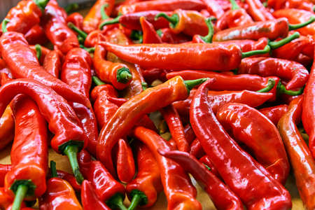 Red hot chili peppers pattern texture background. Close up. Landscape. A backdrop of Red hot chili peppers. Street vegetable market. Group of Red hot chili peppers