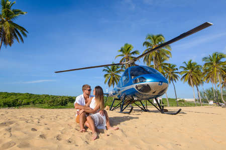 Macao beach. Dominican Republic October 7, 2015. Loving couple resting on the beach in the background with a helicopter. Sightseeing helicopter Фото со стока - 139316929
