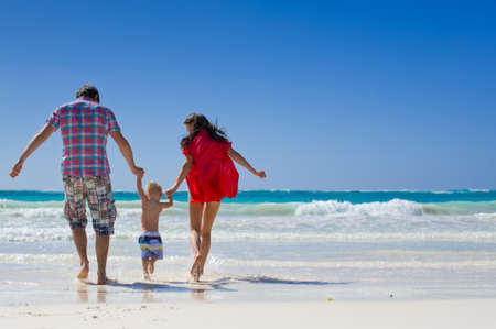 Parents Running Along Beach With Children On Summer Vacation Фото со стока - 139316943
