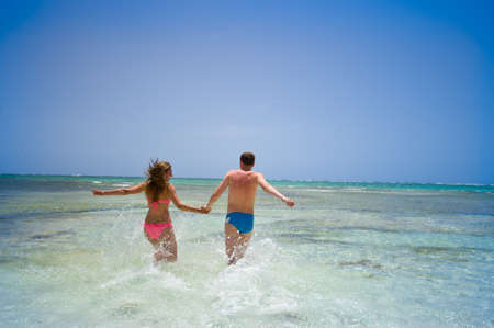 Parents Running Along Beach On Summer Vacation. 04.07.2014 Dominican republic Punta cana Фото со стока - 139316949