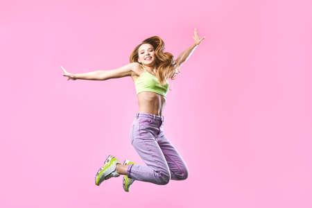 Da ragazza, funky, felicità, sogno, divertimento, gioia, concetto estivo. La ragazza carina felice molto eccitata sta saltando, in abito estivo, su sfondo rosa Archivio Fotografico
