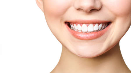 Concepto de estomatología. Retrato parcial de una niña con dientes blancos sonriendo.