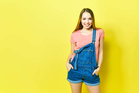 Portrait a pretty girl in denim overalls on a yellow background.
