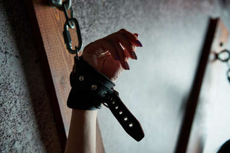 Bound woman slave. Sexy woman in handcuffs. Games for adults in the room BDSM.