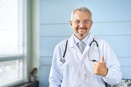 Smiling medical senior doctor with a stethoscope. On a blue background. Medic shows thumb raised up. The concept of humanitys victory over disease