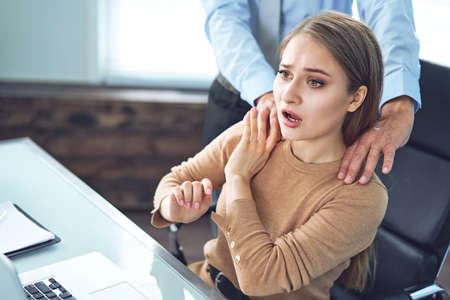 Nękanie, gdy szef dotyka ramienia swojej sekretarki, która siedzi w jego miejscu pracy w biurze