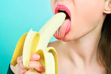 Close-up of sexy woman eating banana isolated on blue.