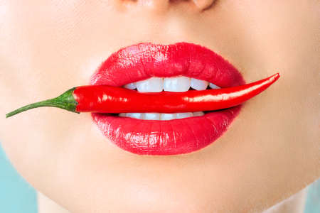 Young woman with chili red pepper isolated en blue background. Sexy female lips. Hot seductive girl