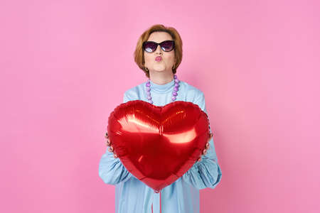 lovely funky old woman blows a kiss. Elderly people. an outpost for dating sites, a wedding agency. Congratulations on Valentines Day