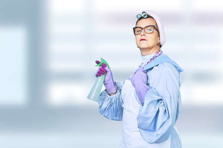 Portrait of old cleaning woman in apron with dust cleaning brush isolated on blue background. special uniform and professional equipment for cleaning Zdjęcie Seryjne