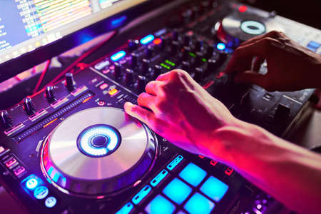 Dj mixes the track in the nightclub at a party.