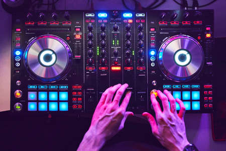 Dj mixes the track in the nightclub at a party Stock Photo