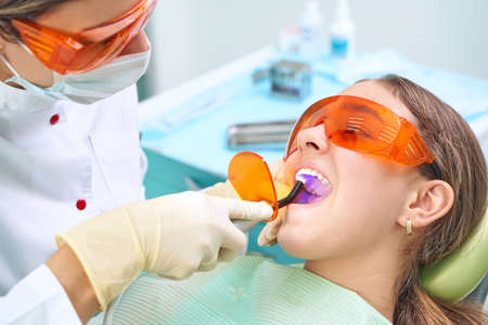 Close up dental treatment procedure in dental office. Dentistry, healthy teeth, medicine and healthcare concept