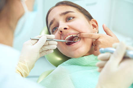 Girl sitting at dental chair with open mouth during oral check up while doctor. Visiting dentist office. Dentistry concept. Фото со стока