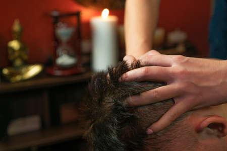 Thai woman gives a man a head massage Фото со стока