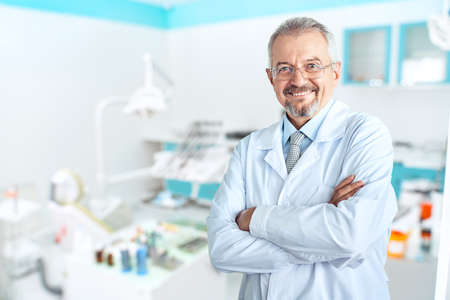 Portrait of glad smiling doctor in white uniform standing with crossed hands on blue dental clinic background