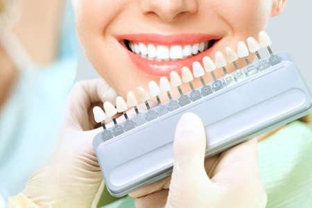 Close up portrait of Young women in dentist chair, Check and select the color of the teeth. Dentist makes the process of treatment in dental clinic office. Teeth whitenning.