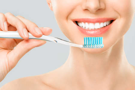 Beautiful smiling woman cleaning her teeth with a toothbrush in a dental hygiene concept. Isolated on white