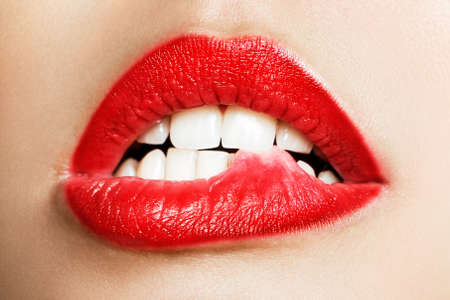 Close-up of the white teeth of a woman biting her lips Archivio Fotografico