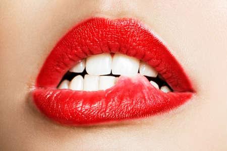 Primer plano de los dientes blancos de una mujer que se muerde los labios Foto de archivo