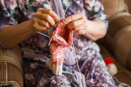 An elderly woman is knitting some socks Zdjęcie Seryjne