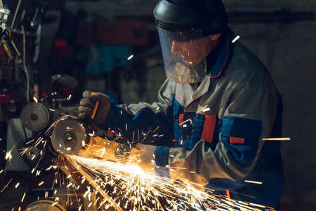 Locksmith in special clothes and goggles works in production. Metal processing with angle grinder. Sparks in metalworking. Stockfoto