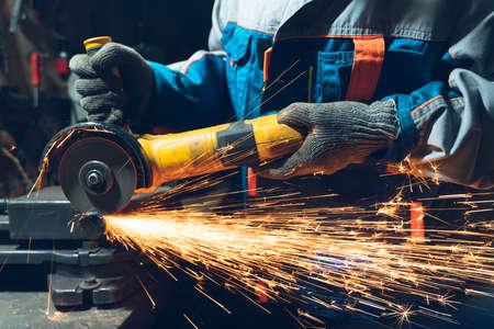 Serrurier en vêtements spéciaux et lunettes travaille en production. Traitement des métaux avec meuleuse d'angle. Des étincelles dans le travail des métaux.