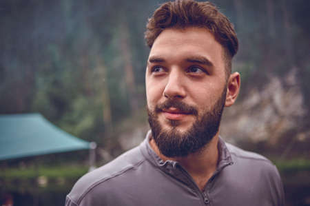 Portrait of a young, bearded man, on, against a background of wildlife. The concept of expedition, adventure and camping life. Stock Photo