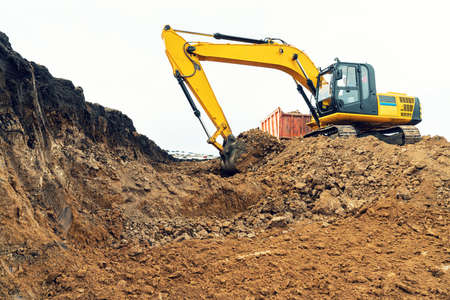 A large construction excavator of yellow color on the construction site in a quarry for quarrying. Industrial image 스톡 콘텐츠