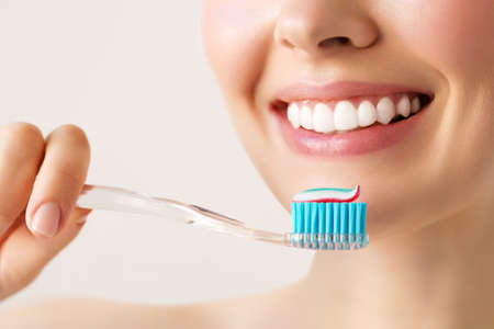 Woman with healthy white teeth holds a toothbrush and smiles. Oral hygiene concept