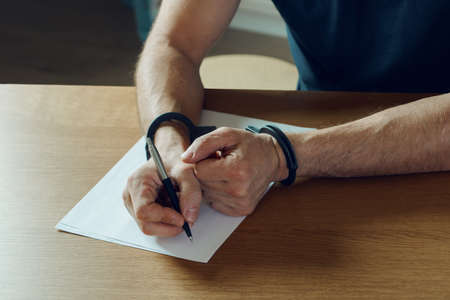 Men hands with handcuffs fill the police record, confession. on top of the police investigative detective. Arrest, bail, criminal, prison. fingerprints, criminal.