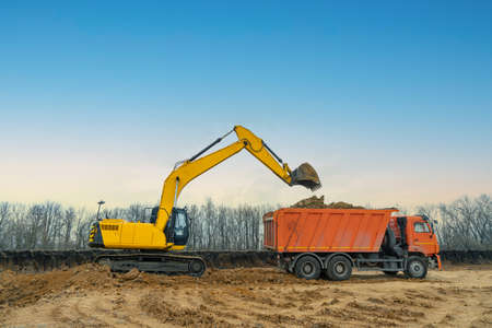 A large construction excavator of yellow color on the construction site in a quarry for quarrying. Industrial image