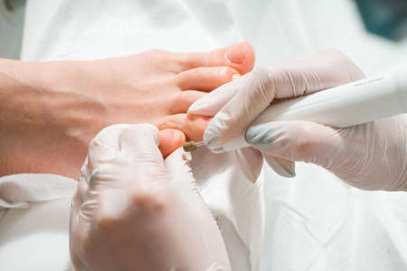 A Podiatrist doctor who takes care of a womans toenails. Cosmetic procedures of the feet Stock Photo