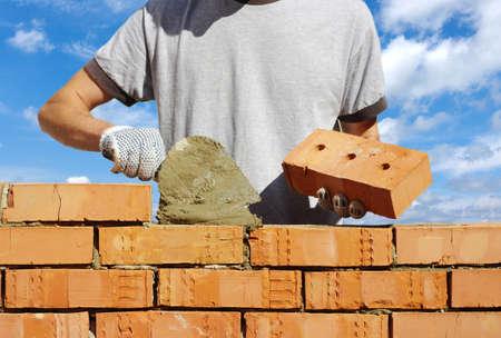 bricklayer: alba�il colocando ladrillos para hacer una pared