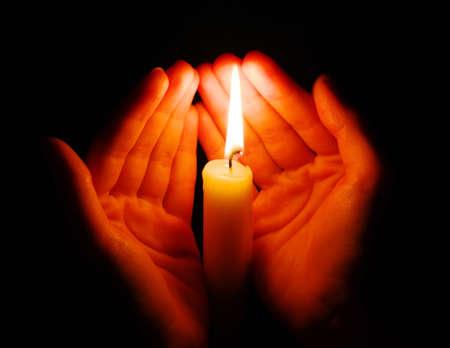 La combustion de la bougie dans une main dans l'obscurité
