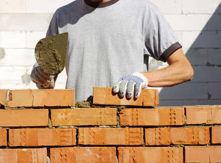cement pile: bricklayer laying bricks to make a wall