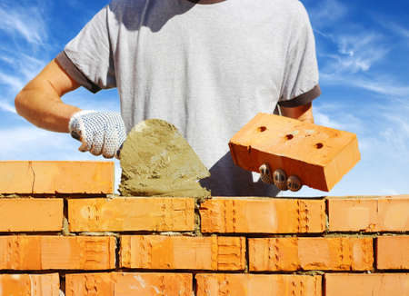 industry worker: bricklayer laying bricks to make a wall
