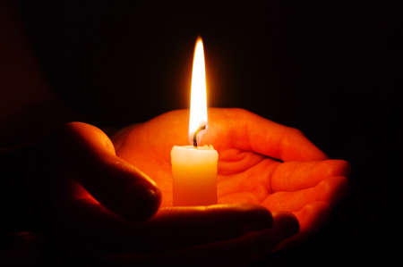 Burning of the candle in a hand in darkness photo