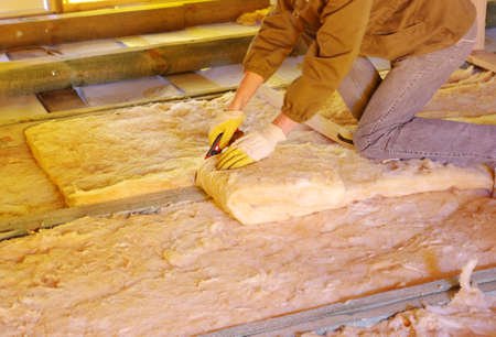Construction worker thermally insulating house attic with glass wool Stock Photo - 14246212