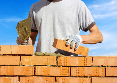 bricklayer laying bricks to make a wall photo